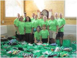 Employees with green shirts take group photo